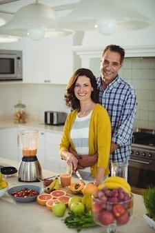 Coppie felici che abbracciano mentre preparano frullato in cucina