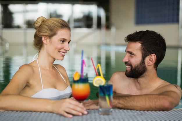 Coppia felice che si gode una vasca idromassaggio e un cocktail