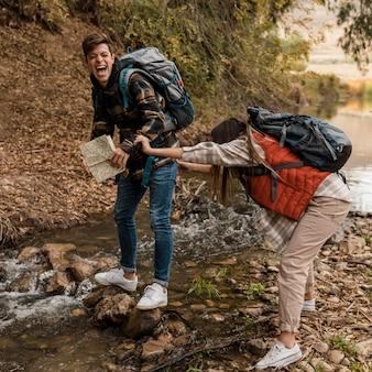 Coppia felice nella foresta ragazza inciampata su una roccia
