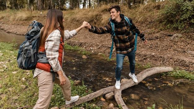 Coppia felice nella foresta mano nella mano su un ponte