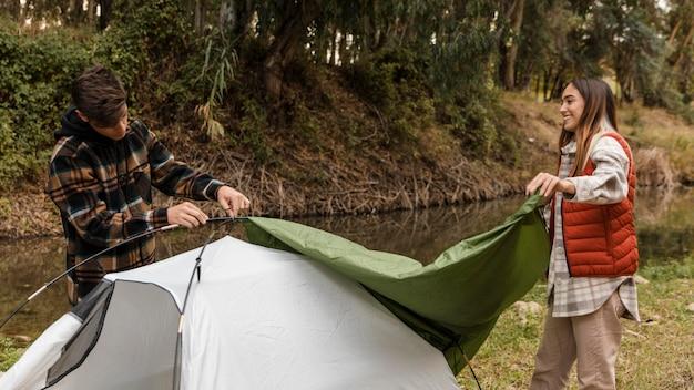 Coppia felice nella foresta prendendo la tenda