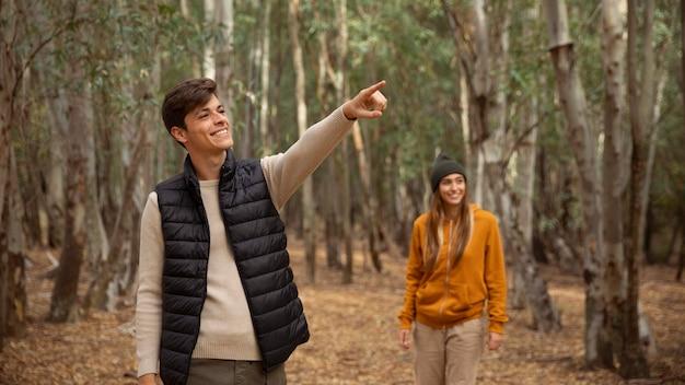 Coppia felice nella foresta camminando tra gli alberi