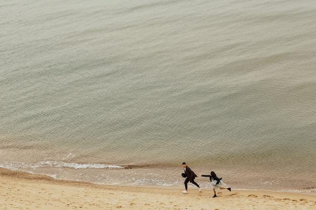 Coppia felice si diverte all'aperto sulla spiaggia sabbiosa.