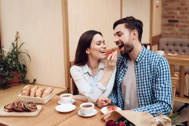 Le coppie felici hanno una data nella caffetteria moderna.