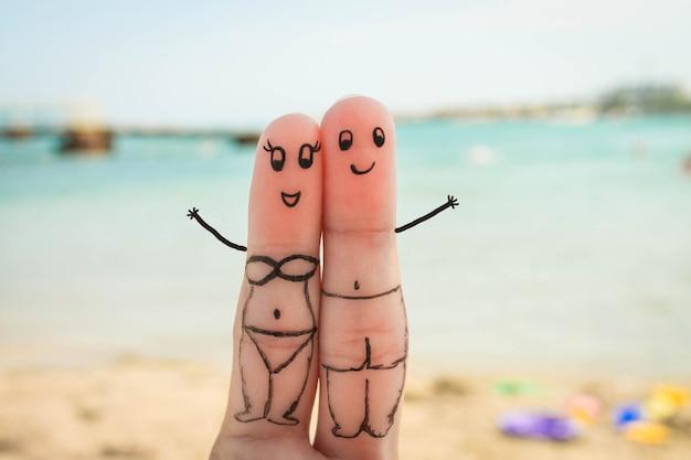 Le coppie felici riposano sulla spiaggia in costume da bagno Foto Premium