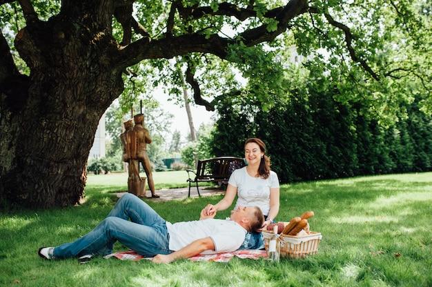 Coppie felici che hanno picnic insieme fuori