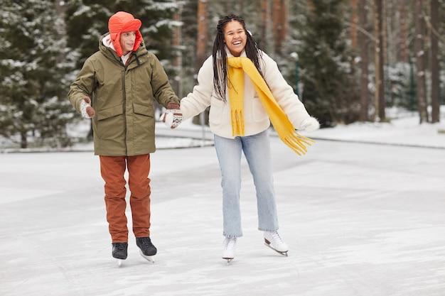 Coppie felici che tengono le mani pattinaggio insieme nella foresta di inverno