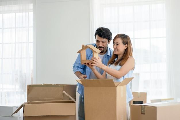 Coppie felici che tengono modello di casa in legno mentre imballano scatole per trasferirsi in una nuova casa