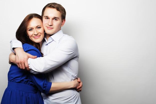 Coppia felice abbracciando su sfondo grigio