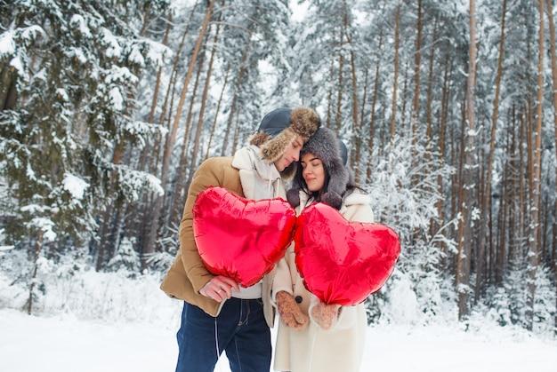 Coppia felice abbracciare e baciare all'aperto nella foresta di inverno. palloncini a forma di cuore