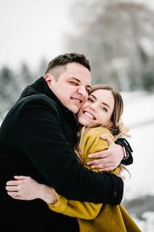 Coppia felice abbracciare e ridere all'aperto in inverno.