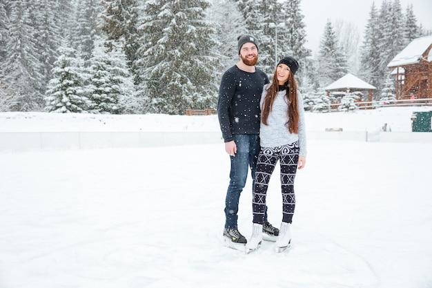 Coppia felice in pattini da ghiaccio che si abbracciano e guardano la telecamera all'aperto con la neve