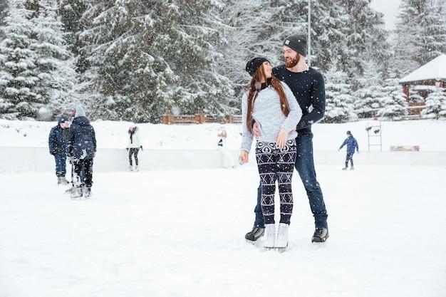 Coppia felice in pattini da ghiaccio che si abbracciano e si guardano a vicenda con la neve sullo sfondo