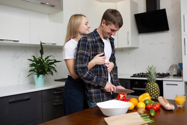 La coppia felice sta cucinando insieme un'insalata sana in cucina