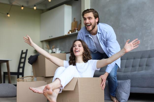 La coppia felice si diverte con le scatole di cartone nella nuova casa al giorno del trasloco, la donna che cavalca seduta in una scatola di cartone mentre l'uomo la spinge.
