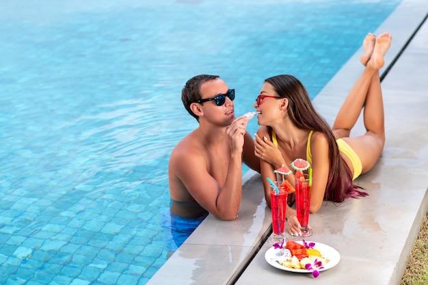 Coppia felice è rilassante in piscina. vacanze estive idilliache. un giovane tratta una ragazza con il frutto del drago. cocktail rossi freschi rossi tropicali