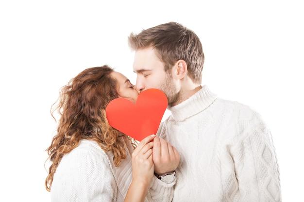 Coppia felice che si bacia dietro un cuore rosso isolato su sfondo bianco