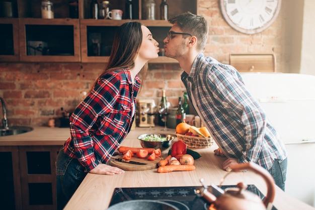 Coppie felici che baciano mentre si prepara una cena romantica. preparazione di insalata di verdure. la famiglia prepara il cibo sano in cucina