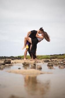 Coppie felici nell'amore balla in spiaggia durante la loro vacanza di fidanzamento