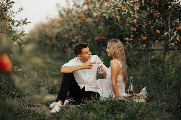 Coppie felici nell'amore hanno un picnic nel meleto estivo. fanno tintinnare i bicchieri con il vino bianco.