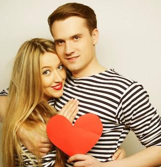 Coppia felice innamorata che tiene cuore rosso