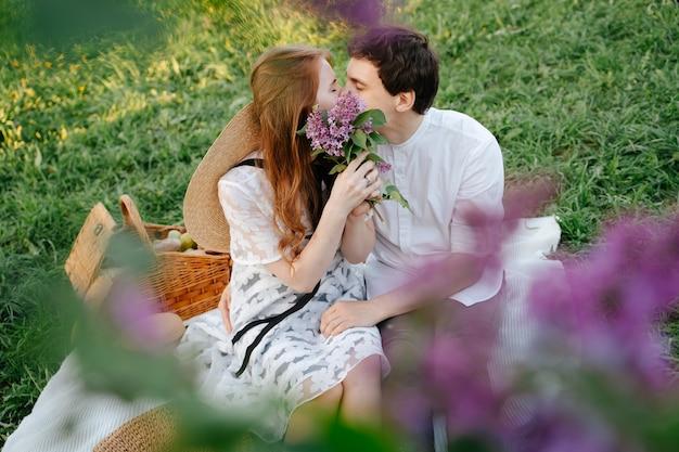 Coppia felice innamorata durante un picnic che si bacia da vicino con lillà viola primaverili