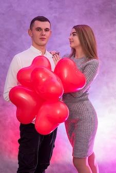 Coppia felice innamorata in posa con mongolfiere rosse a forma di cuore
