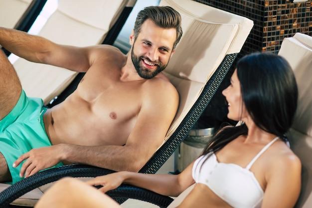 Coppia felice innamorato del resort. bel giovane macho con una bella donna magra sono sdraiati sui lettini nel grande centro termale con piscina e parlano tra loro