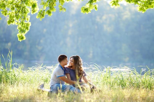 Coppie felici nell'amore che si siede sul picnic di vacanza nella natura