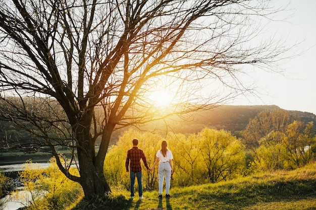 Coppie felici nell'amore in primavera al tramonto.