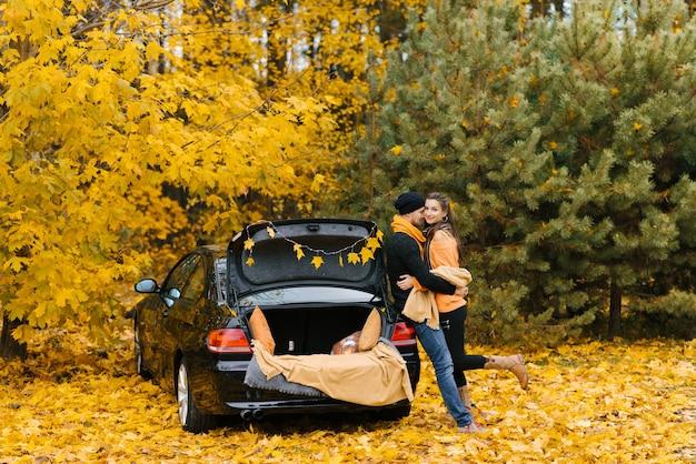 Coppia felice innamorata sta accanto alla loro auto con il bagagliaio aperto nella foresta d'autunno