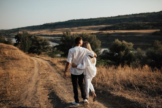 Coppie felici nell'amore che camminano insieme lungo una strada attraverso la campagna.