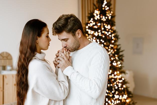Coppia felice innamorato in un accogliente soggiorno bianco con decorazioni natalizie e un albero di natale