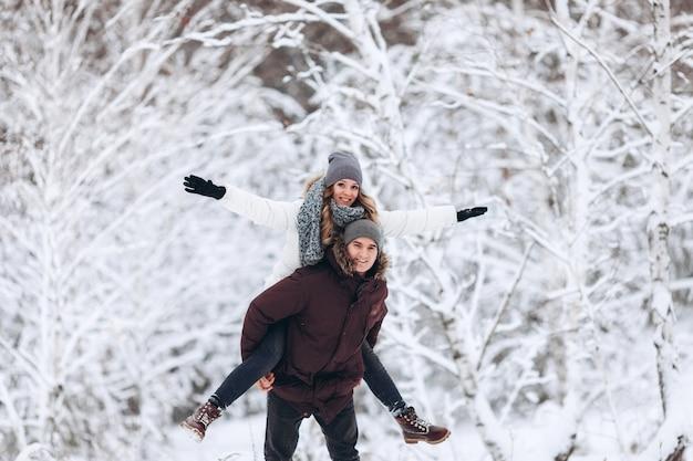 Coppia felice innamorata in inverno in un bosco innevato, una ragazza cavalca sul retro del suo amato ragazzo giocando e sorridendo