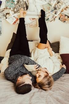 Coppia felice sdraiato sul letto e riposare insieme a casa