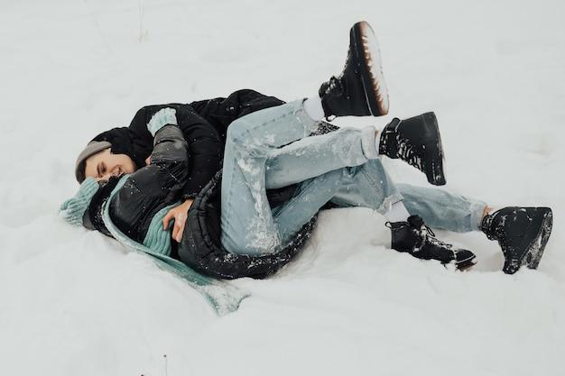 Coppie felici che si trovano sulla neve stanno ridendo e abbracciando