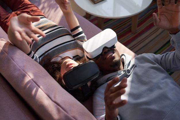 Coppia felice sdraiata sul divano e divertirsi con le nuove tendenze tecnologiche