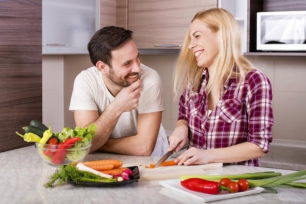 Coppia felice che prepara un'insalata fresca con verdure sul bancone della cucina