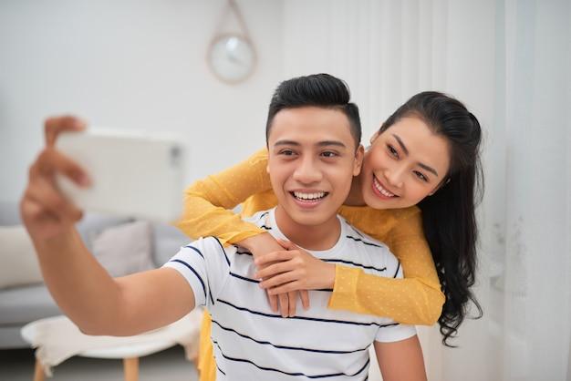 La coppia felice che si fa un selfie in soggiorno
