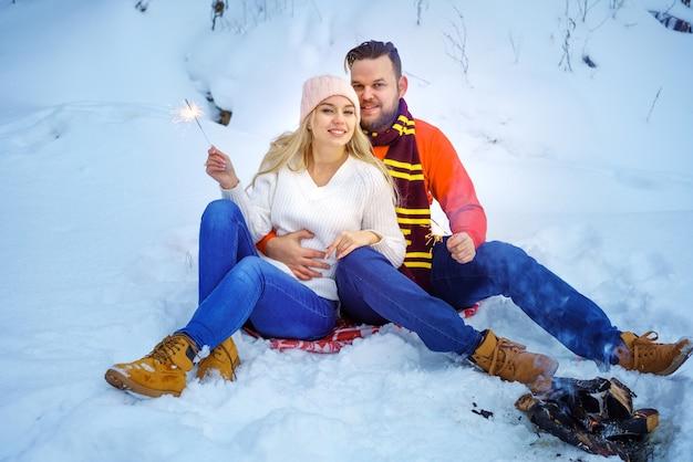Coppia felice uomo e donna che si abbracciano in inverno nella foresta vicino al fuoco con le stelle filanti