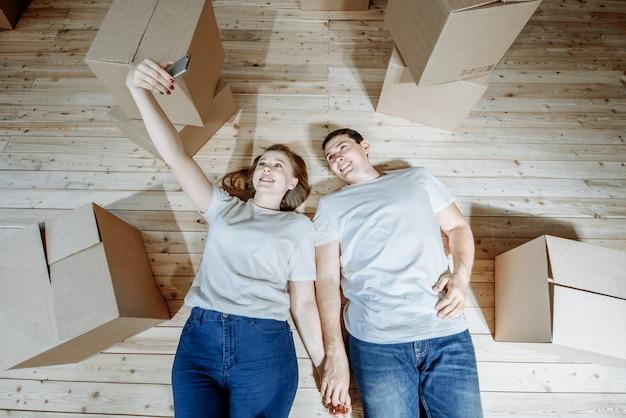 Coppia felice uomo e donna fa selfie con lo smartphone sdraiati sul pavimento tra le scatole per spostarsi in un nuovo appartamento.