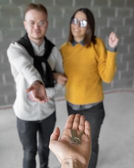 Felice coppia uomo e donna riceve le chiavi del loro nuovo appartamento o casa