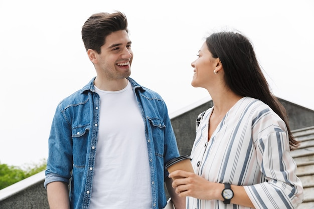 Coppia felice uomo e donna con bicchiere di carta sorridendo e parlando mentre passeggiando giù per le scale all'aperto