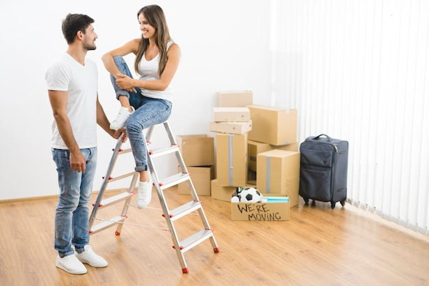 La coppia felice vicino alla scala sullo sfondo delle scatole di cartone
