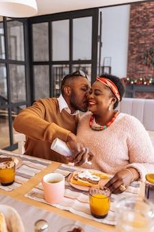 Coppia felice. uomo piacevole piacevole che dà un bacio alla sua ragazza mentre esprime i suoi sentimenti
