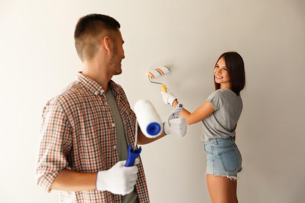Parete felice della pittura delle coppie con il rullo di pittura. ottimo lavoro dei pittori