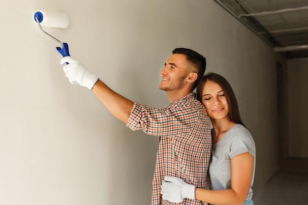 Coppie felici che verniciano una parete con un rullo di vernice