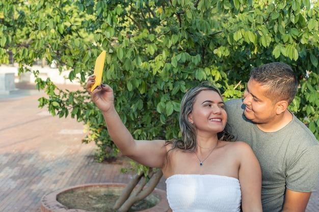 Coppia felice nel parco. coppia felice che scatta foto con il telefono.