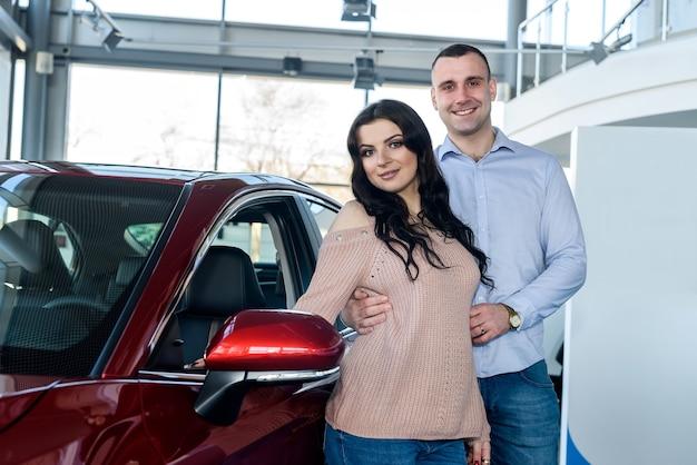 Coppia felice in posa con auto nuove in showroom