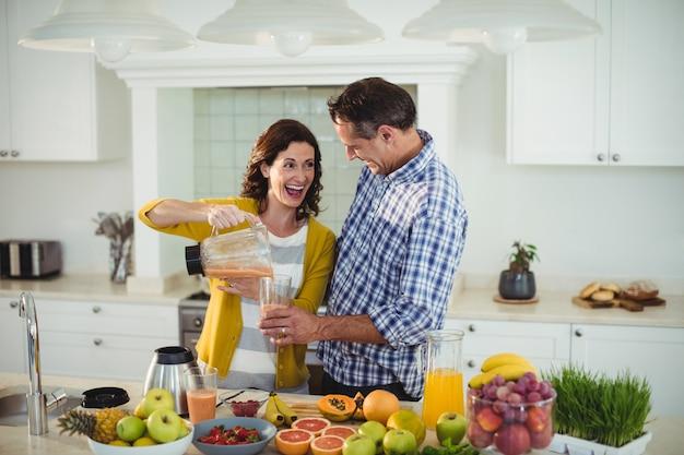 Coppie felici che preparano frullato in cucina